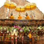 Buddhas mit Sonnenschutz und Opfergaben und Räucherstäbchen im Tempel in Ayutthaya / Thailand